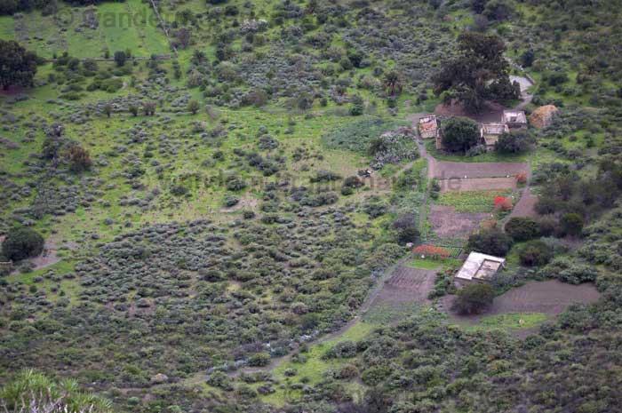 Blick von oben in den Krater mit Bauernhof und Feldern